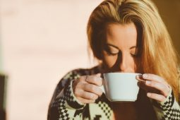 Woman wearing a sweater drinking a cup of coffee